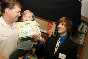 Kye Masino, right, hands a book to Matt Toland and his son Leighton Toland before dedicating the library.