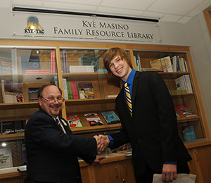 Brad Schaefer, M.D., chief of the UAMS Division of Genetics, left, and Kye Masino shake hands after unveiling a sign designating the Kye Masino Family Resource Library.